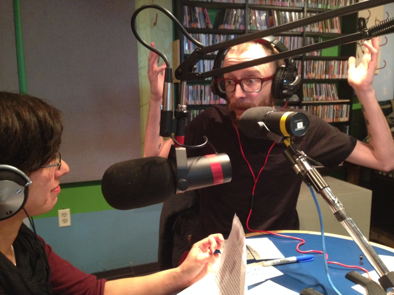 Justin flails his arms in conversation with Emily in the radio studio.